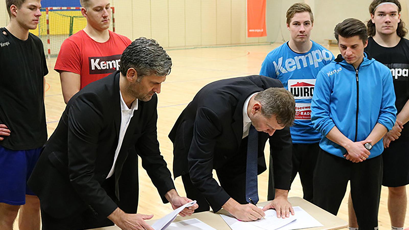 Stephan Stübe (HC EMPOR - Geschäftsführer) und Oliver Brünnich (Vorstandvorsitzender der Rostocker Stadtwerke) bei der Vertragsunterzeichnung.