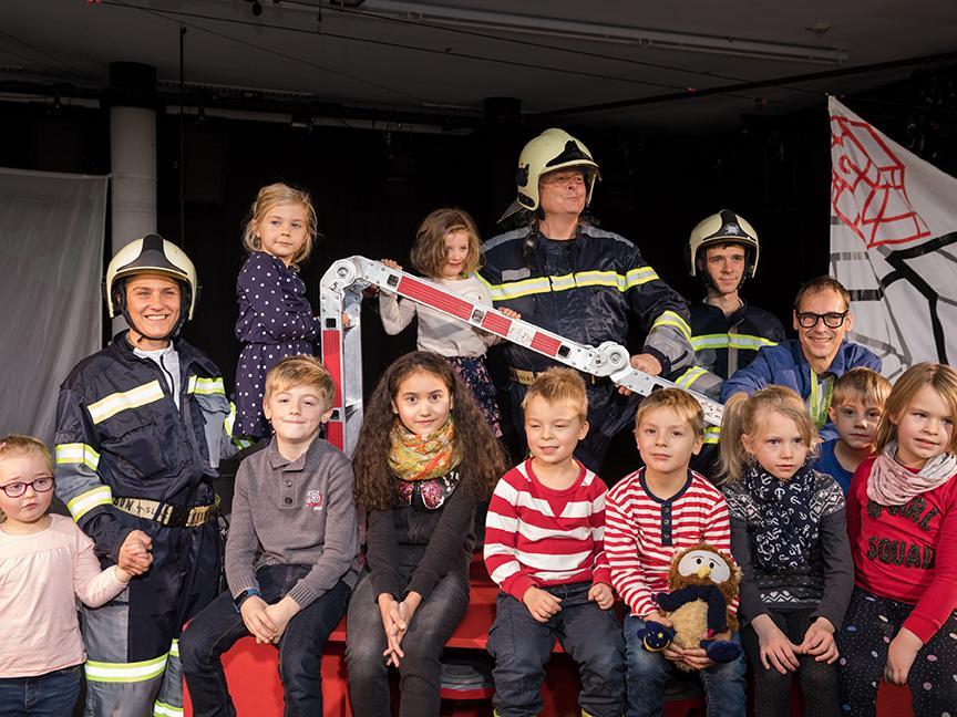 Zehn glückliche Kinder nach der Vorstellung mit den Schauspielern des Volkstheaters.