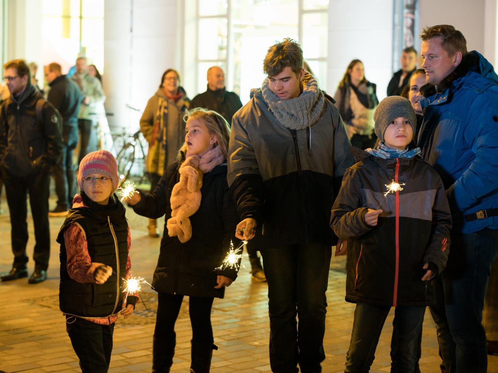Die Kinder erhellen den Uni-Platz mit Wunderkerzen