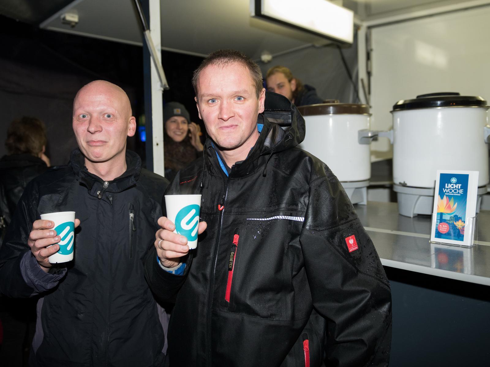 Besucher der Lichtwoche trinken Glühwein für den guten Zweck