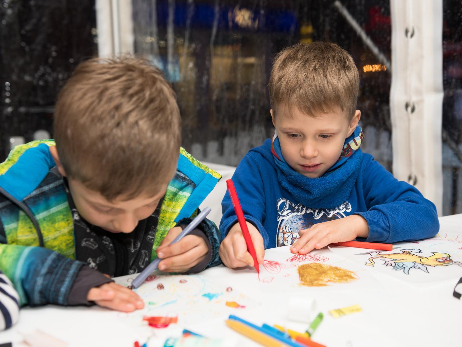 Kinder basteln Laternen für den großen Umzug am Freitag