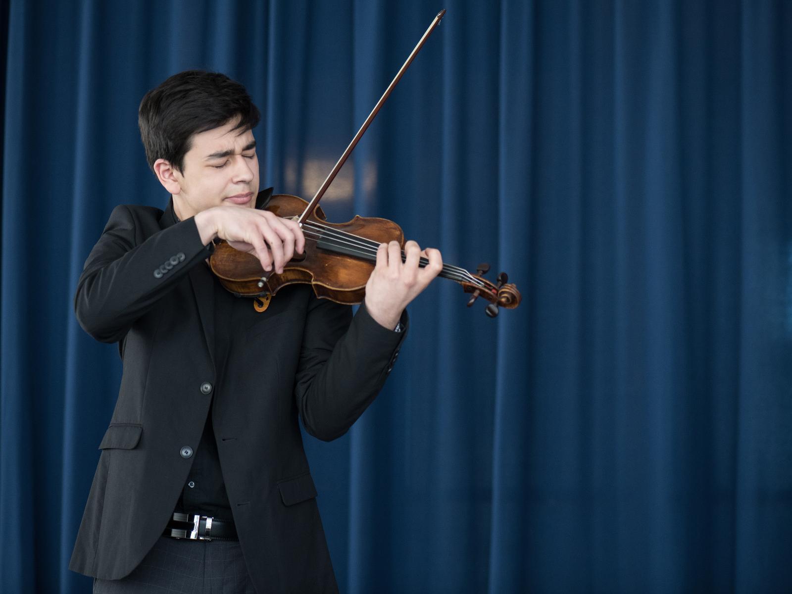 Ein junger Geiger zeigt den Schülern sein Talent.